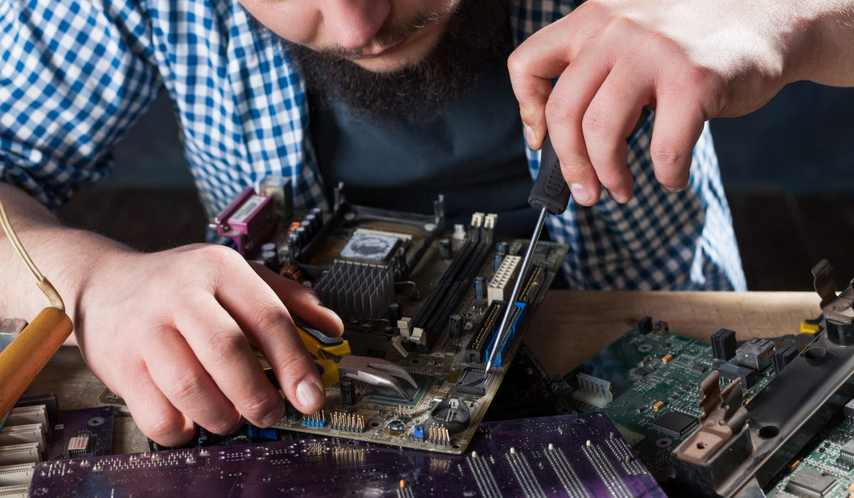 Male service engineer disassembling laptop with screwdriver. Electronic devices repairing technology