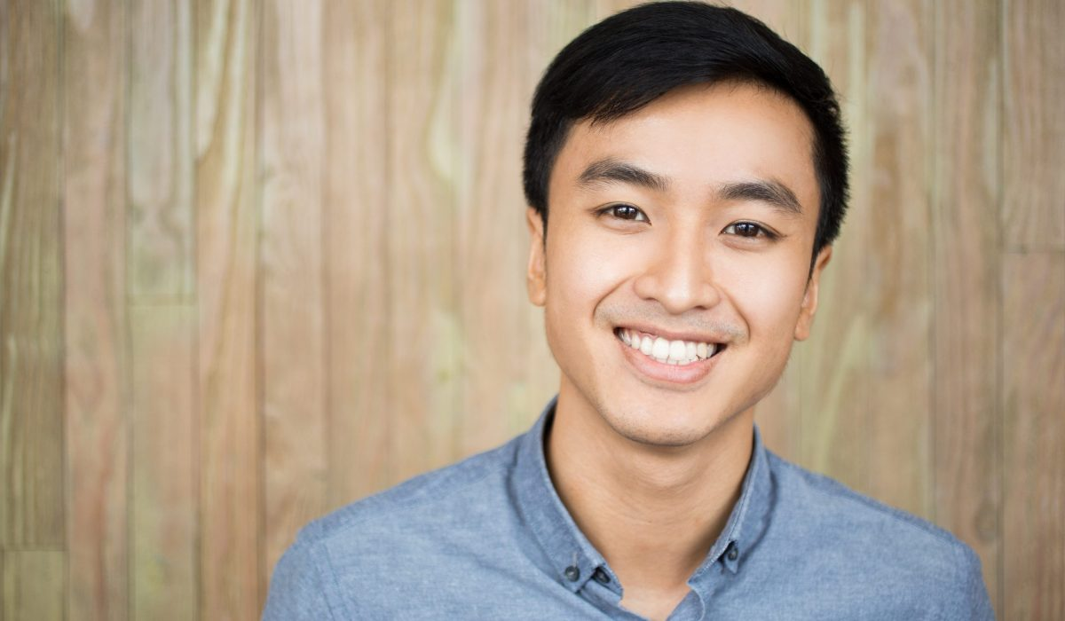 Closeup portrait of smiling young Asian man looking at camera with wall in background. Front view.